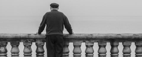 black and white photo of old man looking at the sea